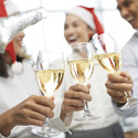 Close-up image of colleagues clinking glasses at Christmas party
